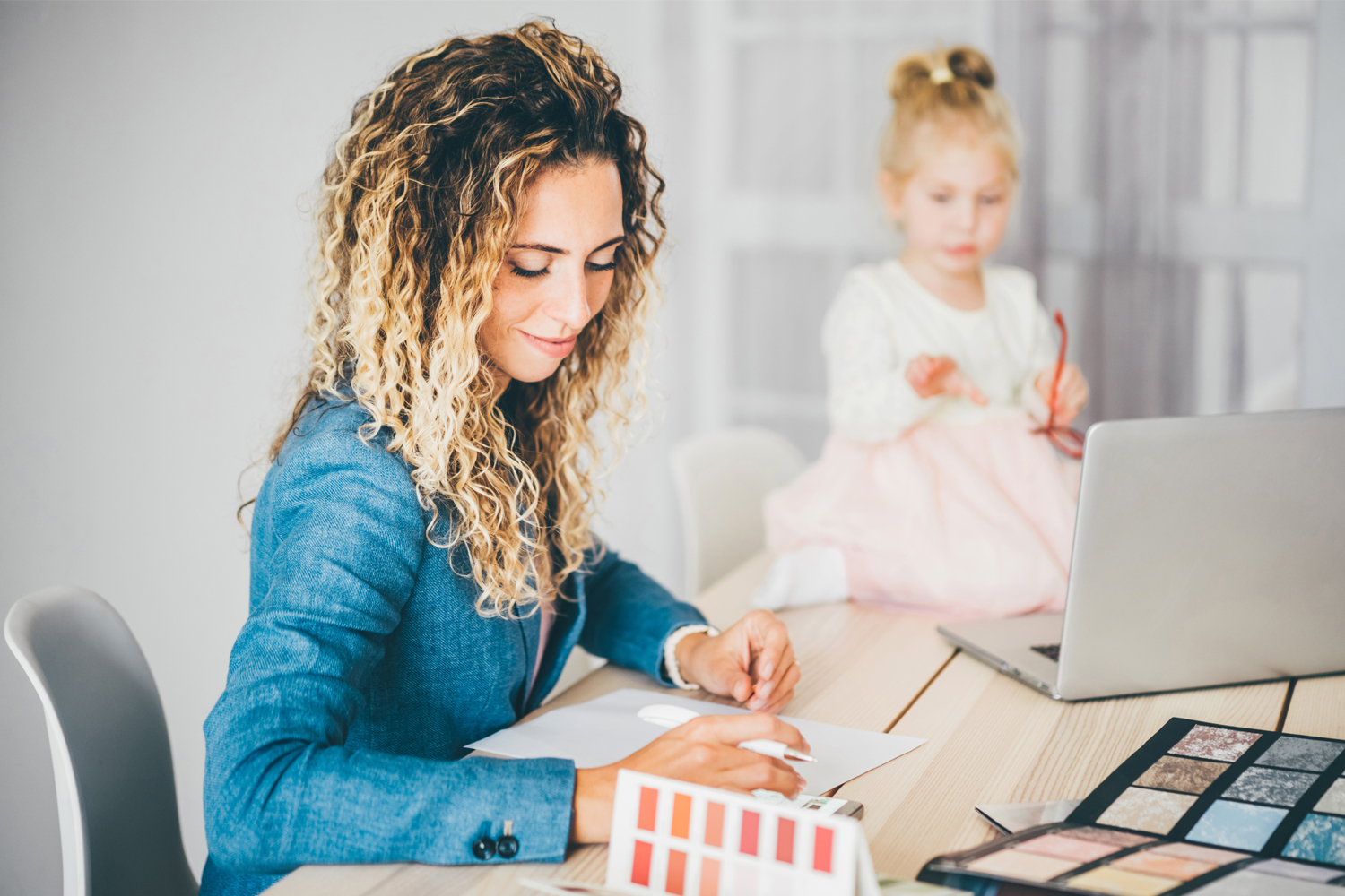 Business mom working at home with kid